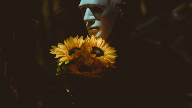 person-wearing-a-mask-holding-sunflowers-2064756